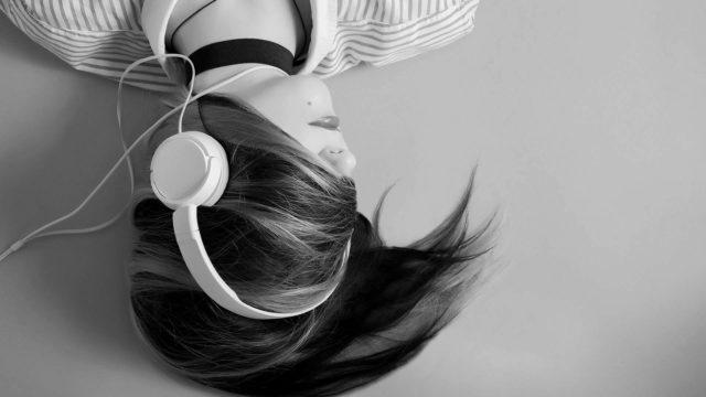 ヘッドホンで音楽を聞く女性 悲しい 切ない