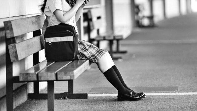 駅のホームのベンチに座る女子高生