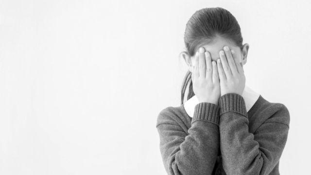 泣いている女子学生 手で顔を覆う