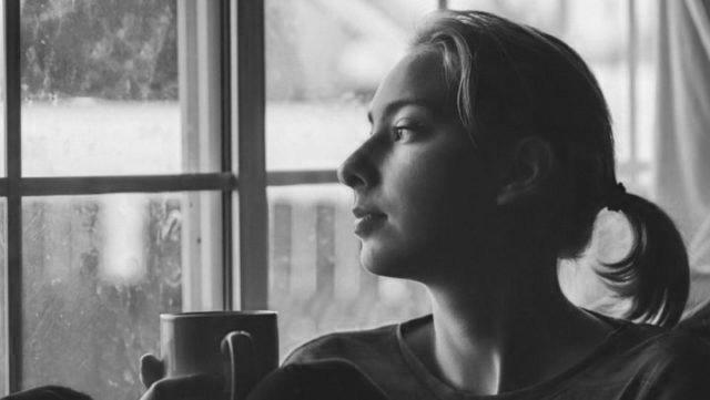 カフェ 喫茶店 窓際で外を眺める女性