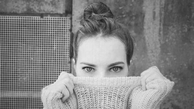 口を隠す女性 視線 見つめる