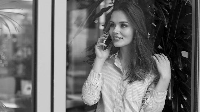 笑顔で電話をする女性 スマホ 窓際