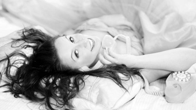 寝転がって電話をする女性 トーク ベッド 笑顔