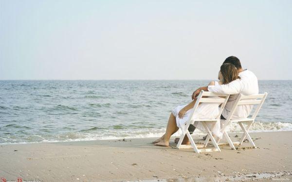 カップル 海 ベンチ 座る 肩を抱く