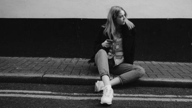 道路に座る女性 スマホ